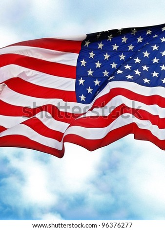 United States flag flying against a cloudy blue sky. - stock photo