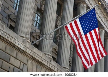 United States flag hanging outside the Department of Commerce building in Washington, DC. - stock photo