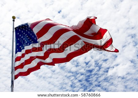 United States flag waving in the wind with beautiful sky in background - stock photo