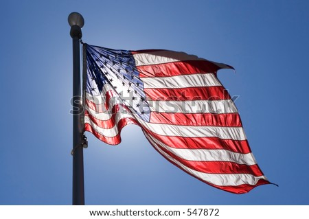 United States Flag waving in the wind with sun behind