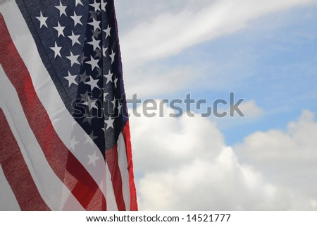 United States flag with partly cloudy sky background - stock photo