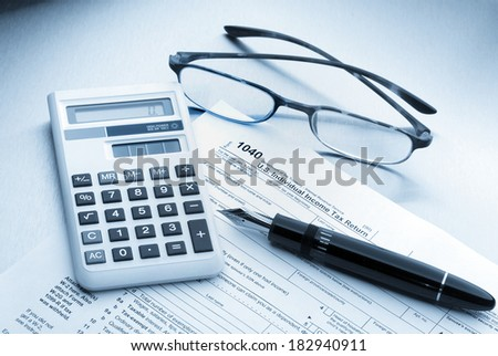 United States Income Tax 1040 Form and Instruction Sheet, Calculator, Pen and Glasses - stock photo