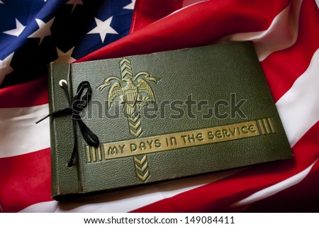 United States Memorial Day remembrance photo of a World War II Military Service photo album with US Flag as a background symbolizing memories of a war veteran's military service and fight for freedom. - stock photo
