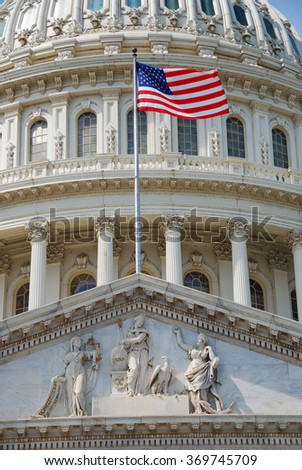 United States national flag in front of capitol building dome in Washington DC.