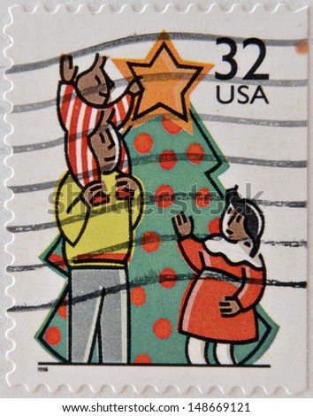 UNITED STATES OF AMERICA - CIRCA 1996: A stamp printed in USA shows a family decorating a christmas tree, circa 1996