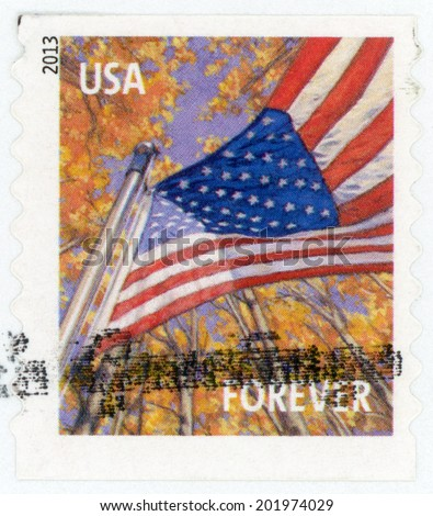 UNITED STATES OF AMERICA - CIRCA 2013: forever stamp printed in USA shows American flag viewed from below flying from pole against background of trees in autumn; flag for all seasons, circa 2013 - stock photo