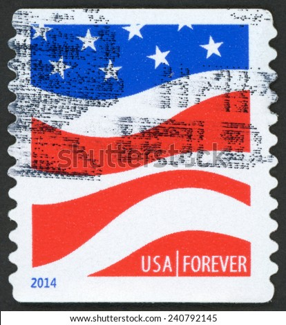 UNITED STATES OF AMERICA - CIRCA 2014: forever stamp printed in USA shows modern interpretation of flying American flag, six wavy stripes and five pointed stars; red white blue; circa 2014 - stock photo