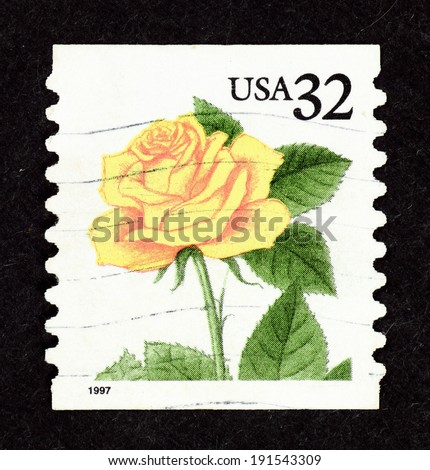 UNITED STATES OF AMERICA - CIRCA 1997: Postage stamp printed in United State of America with image of a yellow rose with green leaves. - stock photo