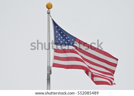 United States of America flag flying on the flagpole. USA flag on the background of a gray cloudy sky