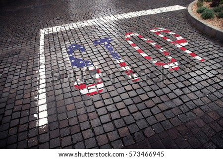 United States of America flag painted on wet paving road floor stop sign.