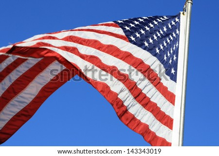 United States of America Flag Waving 'United States of America' flag.  The flag is flying beneath a brilliant blue sky.