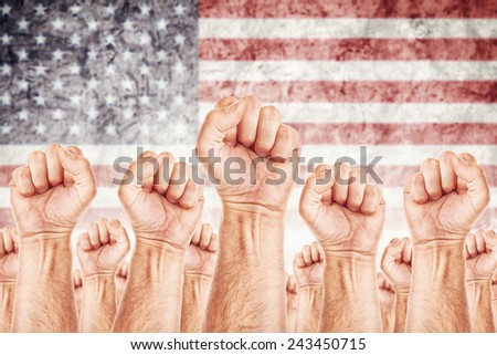 United States of America Labor movement, workers union strike concept with male fists raised in the air fighting for their rights, American national flag in out of focus background. - stock photo