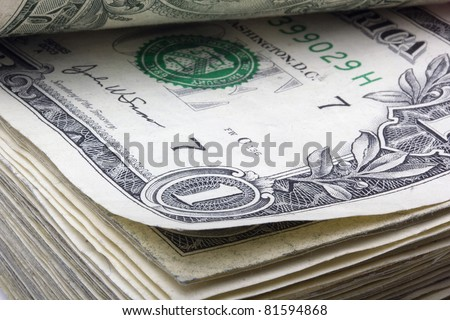 United States one dollar bill laying in a stack of money.
