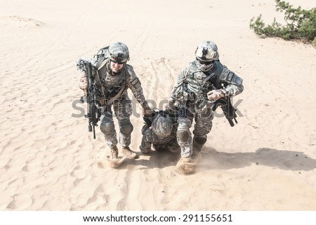 United States paratroopers airborne infantrymen in the desert rescuing their brother - stock photo