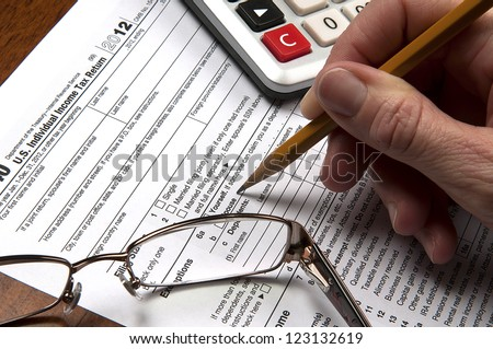 United States tax return form with hand holding sharpened pencil with calculator and glasses - stock photo
