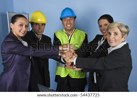 United team of happy architects or engineers with their hands together on blue background - stock photo