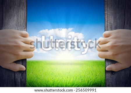 Unity . Hand opening an old wooden door and found Unity word floating over green field and bright blue Sky Sunrise. - stock photo