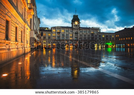 Unity of Italy Square in Trieste, Italy at night during the heavy raining. Illuminated buildings - town hall and cloudy sky. People with umbrellas - stock photo