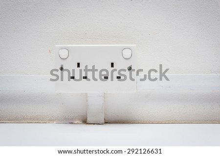 Universal electric socket adapter on white old wall. - stock photo