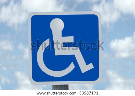 universal wheel chair sign with clouds in the background - stock photo