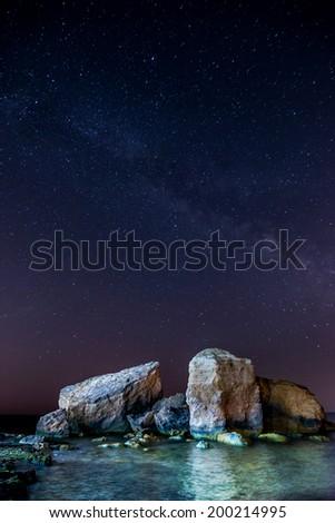 Universe Milky Way and sea mountains. A night sky full of stars light up the sea cliffs at the full moon - stock photo
