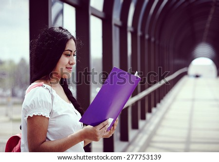 University / college student girl looking happy smiling with book on the bridge