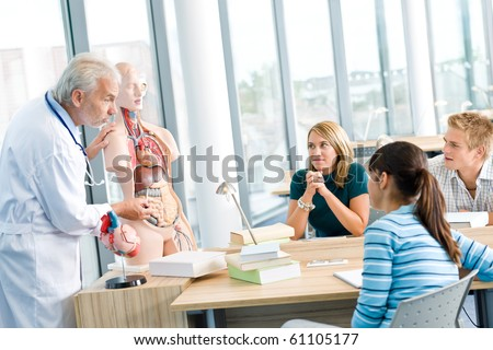 University - medical students with professor and human anatomical model in classroom - stock photo