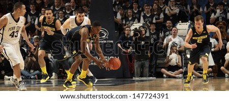UNIVERSITY PARK, PA - FEBRUARY 27:  Michigan's Glenn Robison III starts a fast break against Penn State at the Byrce Jordan Center February 27, 2013 in University Park, PA - stock photo