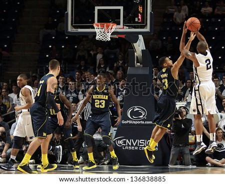 UNIVERSITY PARK, PA - FEBRUARY 27: Penn State's D.J. Newbill shoots over a Michigan  defender at the Byrce Jordan Center February 27, 2013 in University Park, PA - stock photo