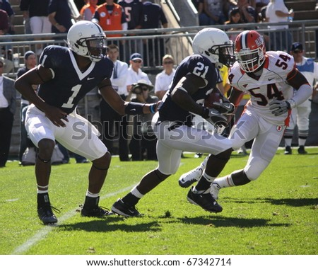 UNIVERSITY PARK, PA - OCT 9: Penn State quarterback Robert Bolden hands the football to No. 21 Stephon Green during a game against Illinois  at Beaver Stadium on October 9, 2010 in University Park, PA - stock photo