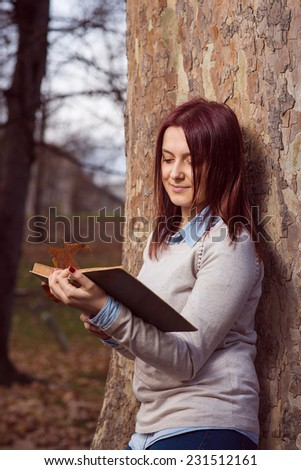 University redhead girl staning in park and reading a book - stock photo