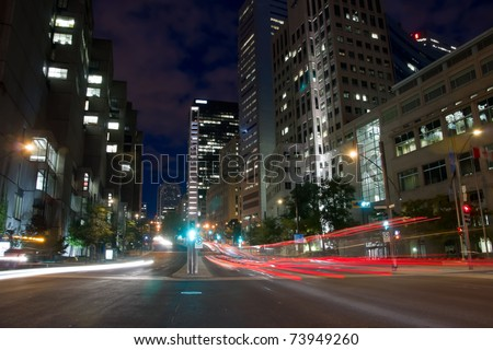 University Street in Montreal with silhouette cars with red rear light and traffic light, early morning to dusk,with office buildings background. - stock photo