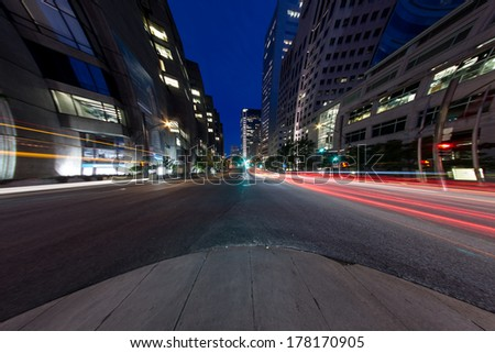 University Street in Montreal with silhouette cars with red rear light and traffic light, with offices buildings background, at dusk. (8mm Circular Fish eye Effect) - stock photo