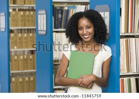 University student holding book in library - stock photo