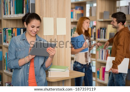 University student looking at tablet with classmates talking in library - stock photo