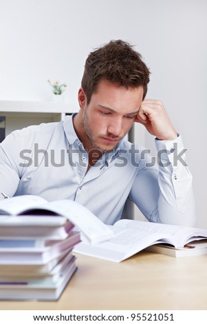 University student with many books at desk learning for exams - stock photo