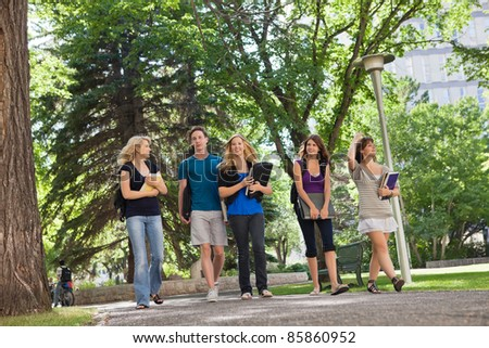 University students walking through the park on their way to college - stock photo