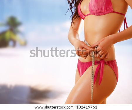 Unknown girl in bikini with tape-measure at sea - stock photo