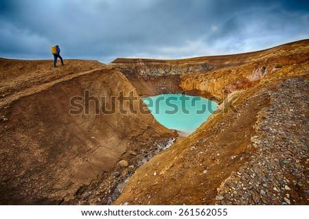 Unknown hiker approaches small crater lake Viti near Askja volcanic lake - stock photo
