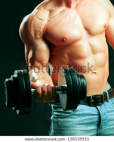 Unknown muscular man working out with dumbbells over black background - stock photo