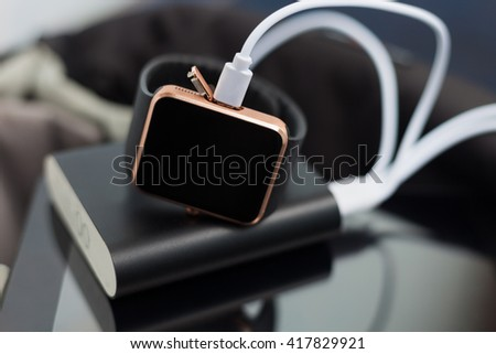 Unknown smart wrist watch charging from a travel powerbank charger. Travel and stay connected to the media networks form anywhere you want.