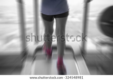 Unknown woman running in gym from back side in pink shoes with motion radial blur split-tone - stock photo
