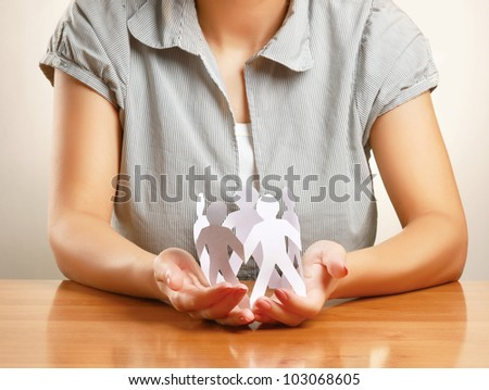 Unknown woman taking care about paper people isolated on grey - stock photo