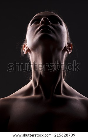 unknown woman with her face in shadow looking upwards
