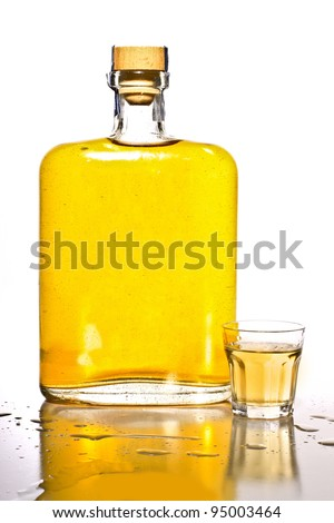 Unlabeled bottle of tequila with a filled shot glass. - stock photo