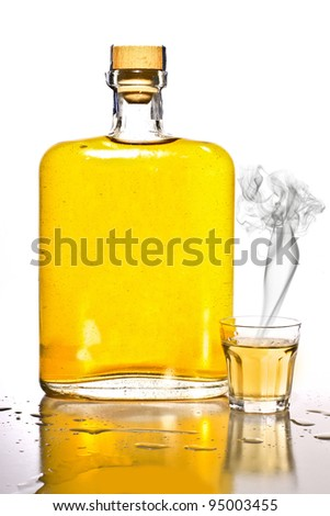Unlabeled bottle of tequila with a filled shot glass with smoke. - stock photo
