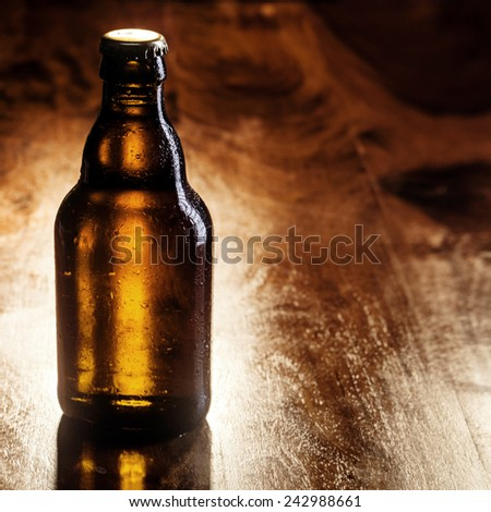 Unlabeled unopened brown bottle of cold beer standing on a wooden bar counter with copyspace for your advertising - stock photo