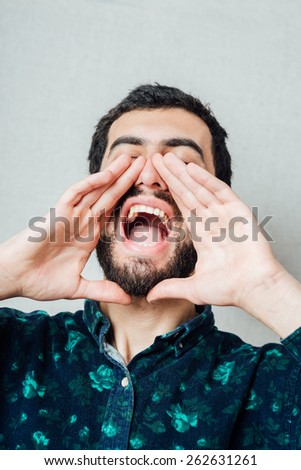 Unleashed emotions. Furious young bearded man shouting while standing against grey background