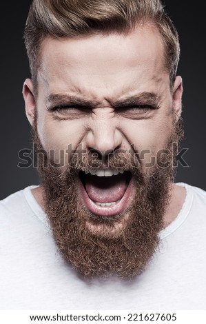 Unleashed emotions. Portrait of furious young bearded man shouting while standing against grey background - stock photo