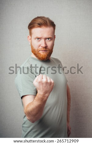 Unleashing his emotions.  Portrait of handsome Young hipster red bearded man wearing orange tshirt and showing his fist with angry face expression while standing against white background - stock photo
